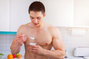 shirtless man taking Progentra eating brogurt yogurt