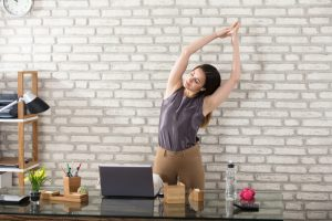 woman in office doing overhead stretches