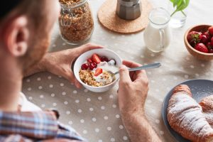 man taking Progentra eating bowl of brogurt yogurt with oats