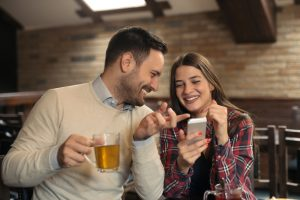 man leans in on woman at bar and confident