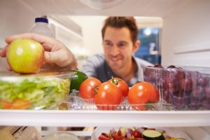 man picking apple from fridge after taking his Progentra pills