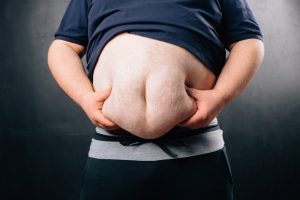 obese man squeezing belly fat